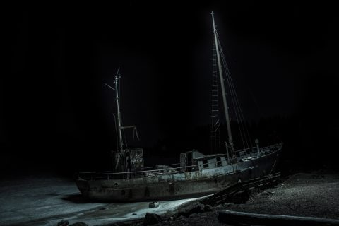 Artwork by Petri Juntunen presenting abandoned fishing vessel ashore in the dark