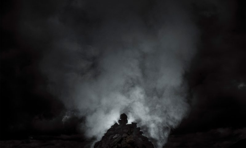 Mist and fog rises from a monolith back lit by artificial light