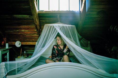 girl sitting on bed under mosquito net