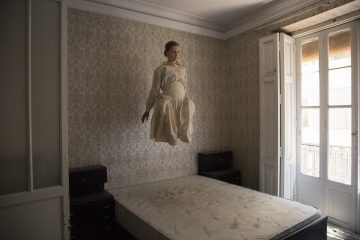 Woman is photographed in a period dress, in an old abandoned house. She appears to be levitating above a bed